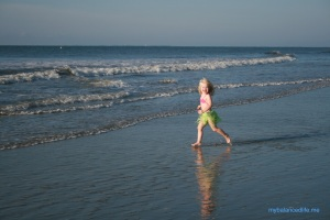 little blonde girl in a grass skirt running in the surf