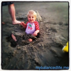 little blonde girl buried in sand